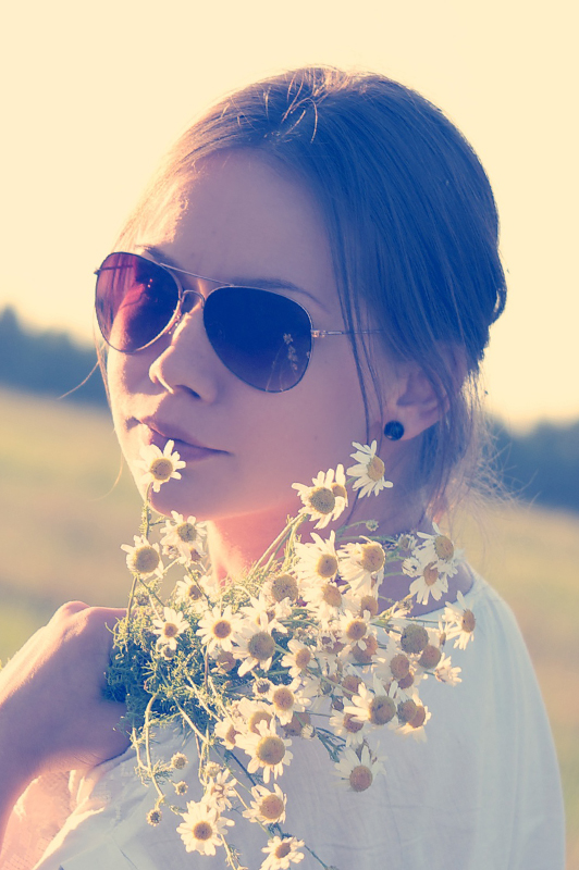 Girl with sunglasses holding flowers.