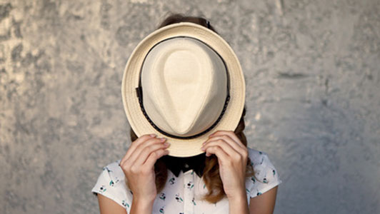 young woman hiding face behind straw hat