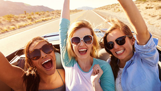three woman enjoying time in car on road trip