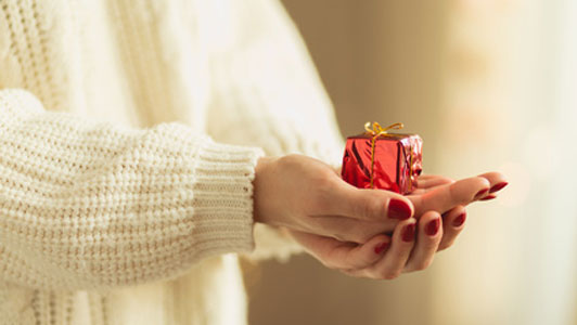 small gift in hands of woman