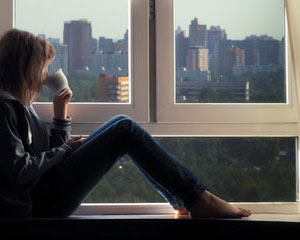 woman sitting on window sill reflecting on view of city drinking a cup of coffee