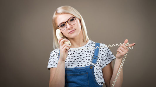 young woman in overalls talking on the phone