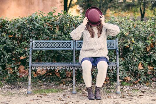 woman hiding behind hat