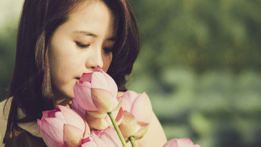 Girl smelling pink tulips.