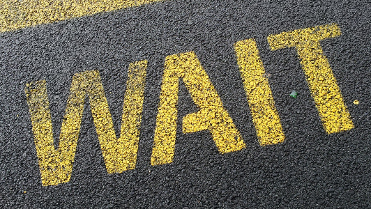 Sign on the road saying 'wait'