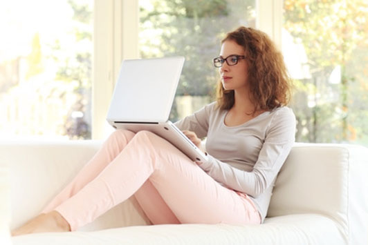 girl sitting on couch wearing glasses looking something up
