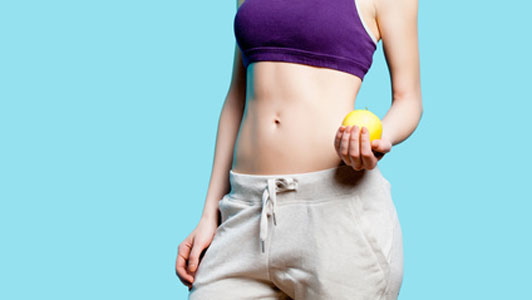 flat stomach of woman holding apple