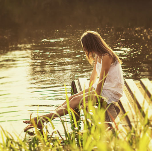 girl sitting by river