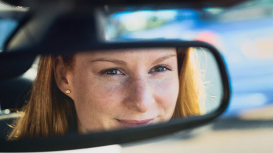 rear view mirror reflection of woman smiling in car