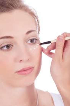 Woman applying concealer on her face