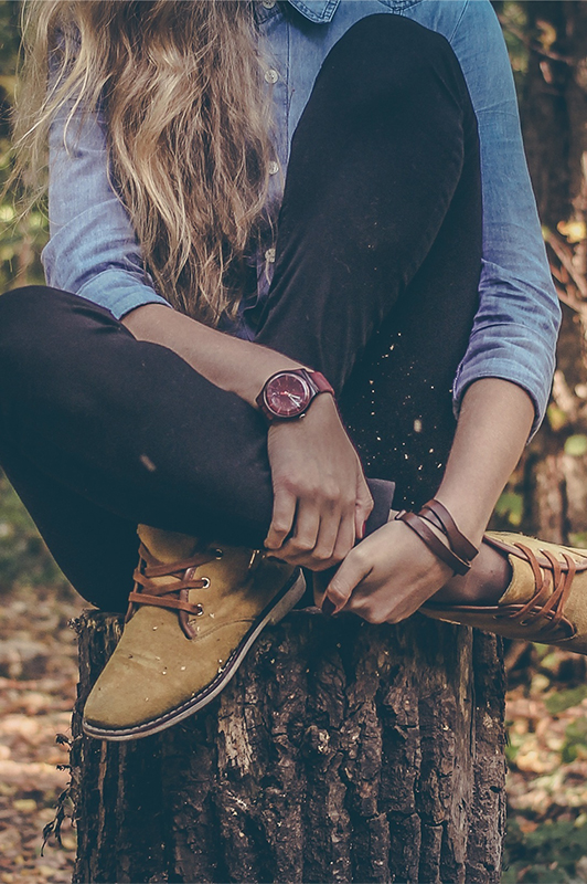 Girl sitting on a tree stump.