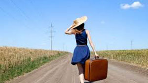 woman in blue dress carrying luggage walking down road into the distance