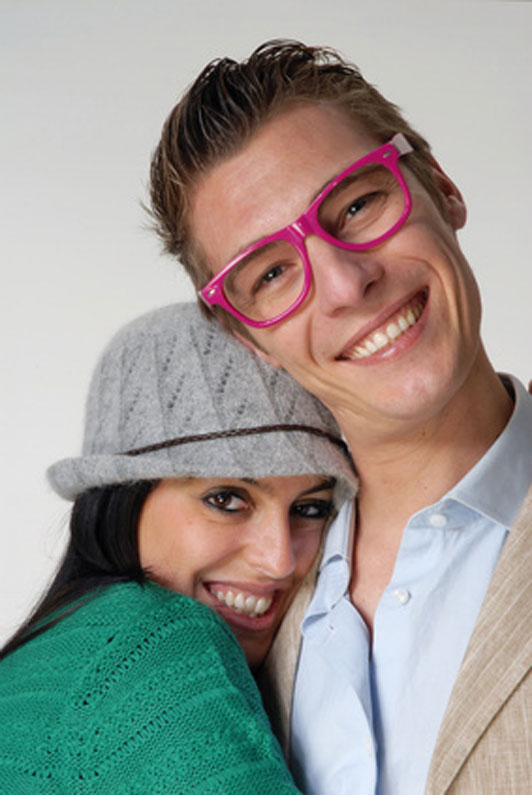 girl in grey beanie and guy in pink eyewear in embrace