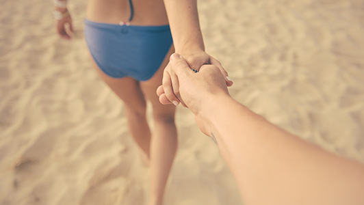 Girl in a bikini holding guy's hand.