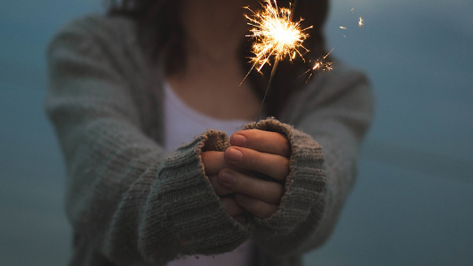 Girl in a sweater holding a sparkler.