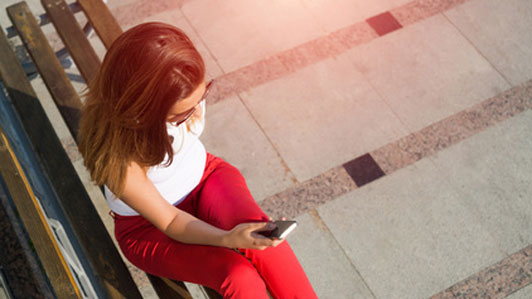 young woman wearing red pants with white headphones around neck holding phone sitting alone on bench
