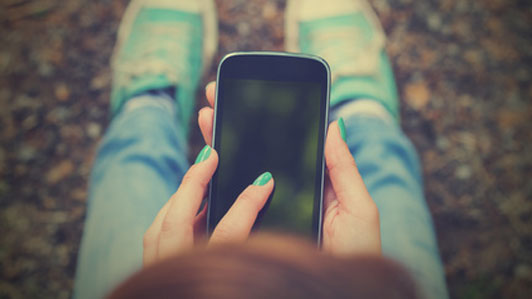 woman sitting on ground with phone