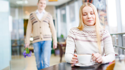 woman having coffee unknowingly being brought flowers by a man