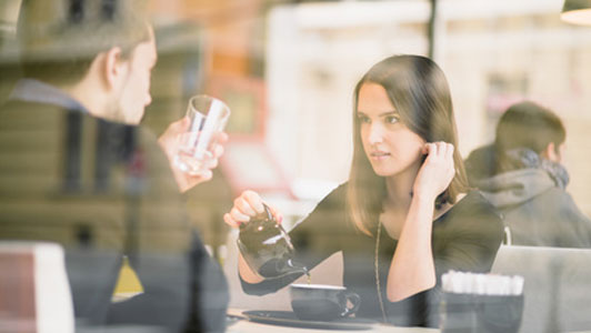 woman attentively listening to guy holding cup at coffee shop