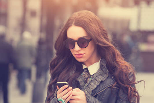girl in sunglasses texting