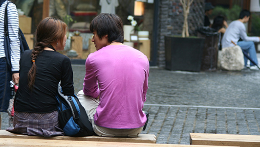 A couple sitting on a bench outdoors.
