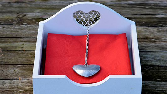 Red napkins in a box with a silver heart on a chain