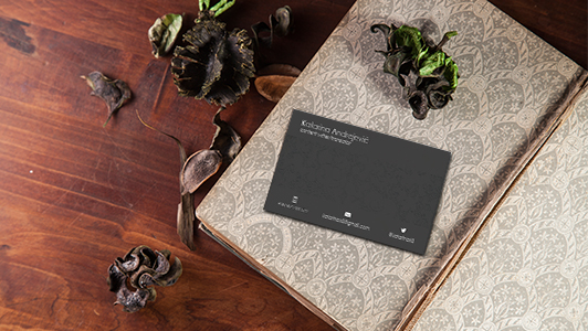 Black business card in a notebook, dry flowers placed around it.