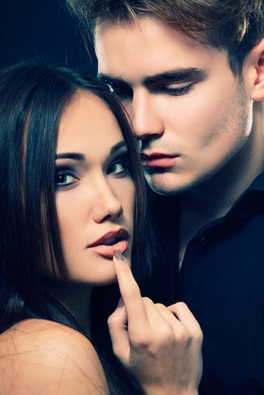 couple in embrace with woman pressing pointer finger on lips