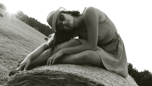 Girl in a dotted dress and a hat sitting on a bale of hay