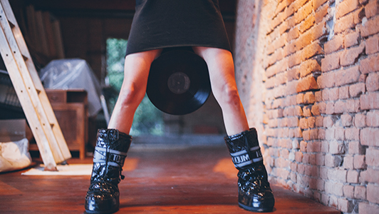 Girl in black dress and boots holding a vinyl between her legs