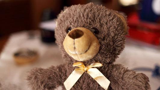 Urso de peluche marrom com fita amarela