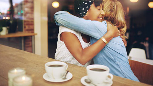 two friends hugging in cafe