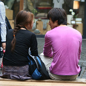 two people sitting on bench together