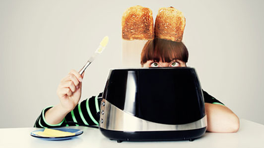 woman holding butter knife watching toast jump out of toaster