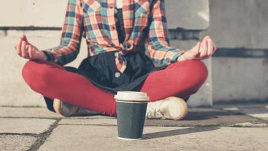 woman meditating in front of cup in street