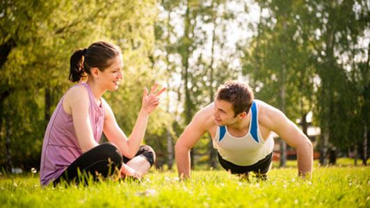 woman encouraging man doing push ups