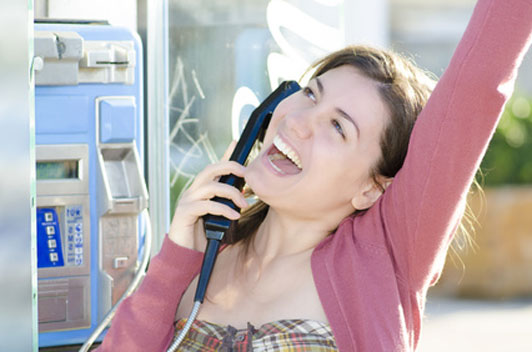 girl making a call on a pay phone