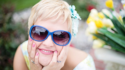 Girl with short hair and blue sunglasses resting her head on her hands.