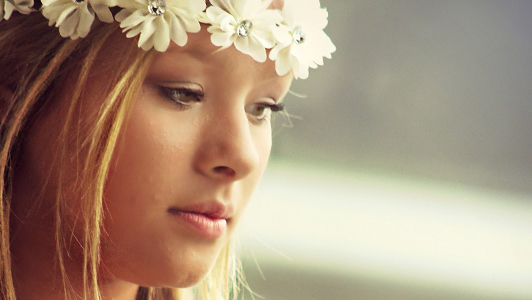 Girl with flowers in her hair looking down.