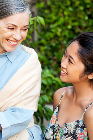 young woman talking cheerfully with elderly