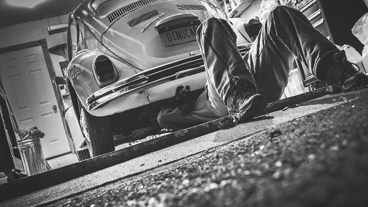 Guy lying under a car and repairing it.
