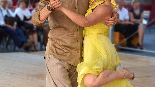 Girl in yellow dress dancing with a guy in a shirt.
