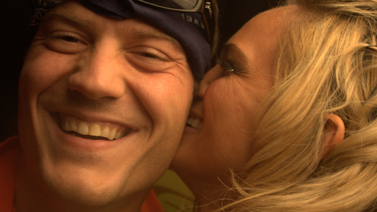 Blonde girl kissing a smiling guy on the cheek.