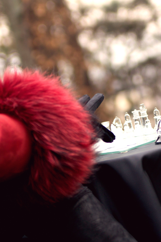 Arm in red coat with leather glove moving a chess piece.