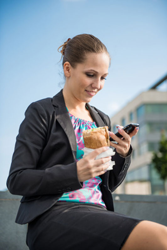 young woman eating and working with phone