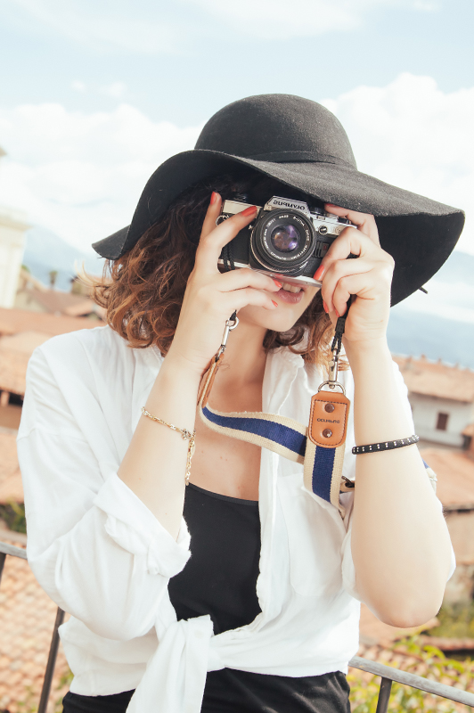 Girl with a hat holding a camera.