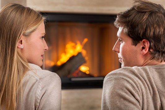 couple gazing at each other in front of fireplace