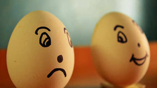 Two eggs: one with sad and one with happy face drawn on it.