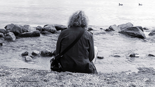 Guy with long curly hair wearing a jacket sitting near a lake.
