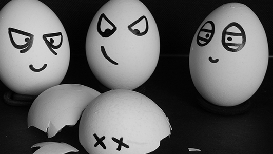 Three eggs with mean-looking faces standing over a broken egg shell.